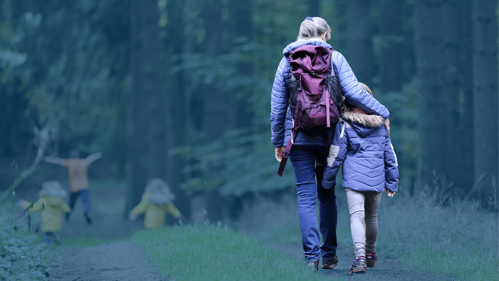 Caregiver and children walking in a forest